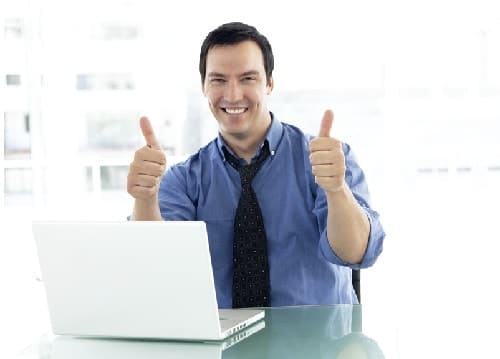 man working on computer with a thumbs up
