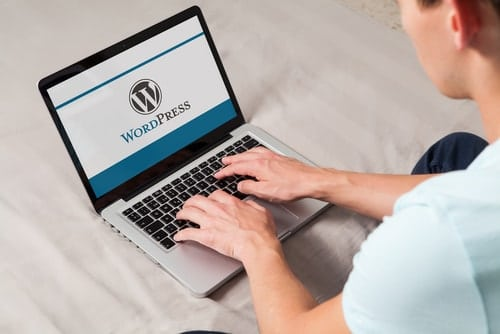 Man typing on the keyboard with WordPress brand logo on computer screen